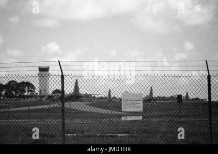 A restricted area sign on a miliary airbase fence in black and white. - Stock Photo