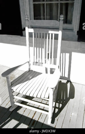 A white rocking chair on an old white porch. - Stock Photo