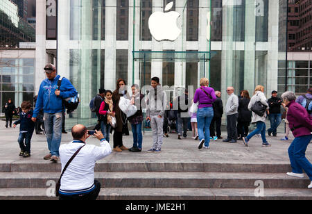 NEW YORK CITY - APRIL 1: Visitors take family pictures at Apple's flagship 5th Avenue store in New York City on - Stock Photo