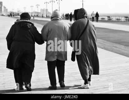 Three elderly women friends in coats walking together arm in arm outdoors in winter. Black and white. Seen from - Stock Photo