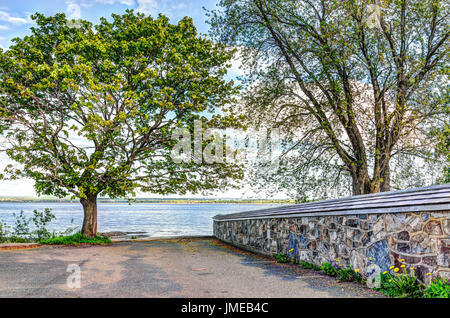 Landscape view of Saint Lawrence river from Ile D'Orleans, Quebec, Canada in summer with stone church wall - Stock Photo