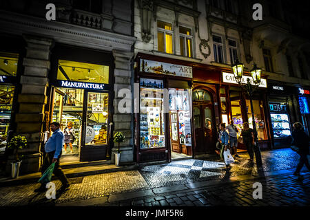 Shoppers and tourists go out for some evening shopping in the Praha district of Prague. The stores are lit up nicely - Stock Photo