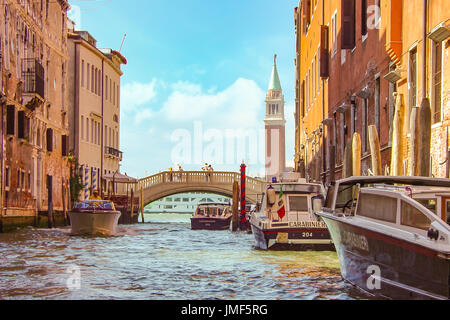 Muted colors and soft focus image of a beautiful day in Venice with the Bell Tower and bridge with couple on it - Stock Photo