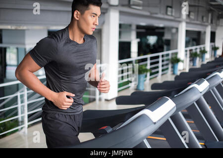 Young Chinese man running on treadmill in gym - Stock Photo