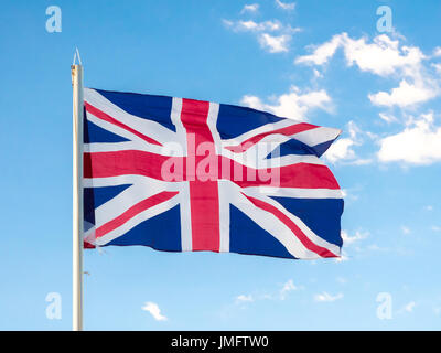 Union Jack, traditional United Kingdom flag, waving in blue sky, copyright space - Stock Photo