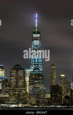 One World Trade Center Centre Lit At Night With Buildings Below, New York - Stock Photo