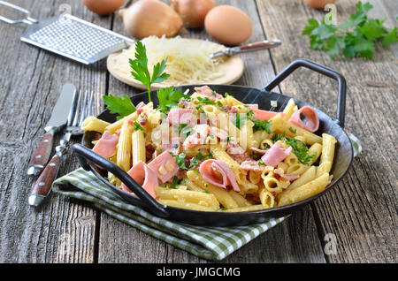 Pasta with boiled ham and bacon bits, cheese and eggs in a pan, grated cheese in the background - Stock Photo