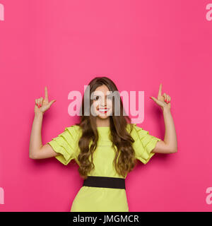 Smiling young woman in lime green dress pointing up and looking at camera. Waist up studio shot on pink background.