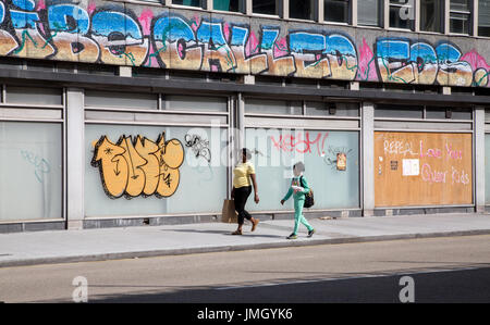A mother and daughter walking past a run down building in Dublin city, Ireland. - Stock Photo