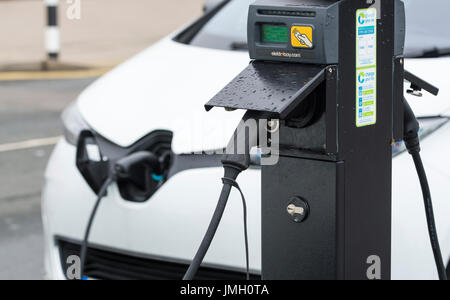 EV charging point with a small electric car plugged in while charging its batteries in Brighton, East Sussex, England, - Stock Photo