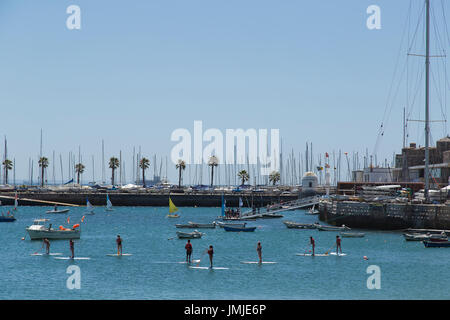 Board surfers in the coastal town of Cascais Portugal - Stock Photo