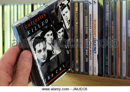 Keep Your Distance, Curiosity Killed the Cat 1987 debut CD being chosen from a shelf of other CD's, Dorset, England - Stock Photo