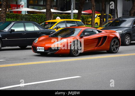 Orange new McLaren drives down a main street in Taipei, Taiwan, causing everyone to turn and stare at it.