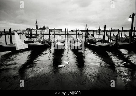 Evening image of tied up Gondolas battered by the waves close to the Sant Marco Square in Venice, Italy. Date: 03/2010. - Stock Photo