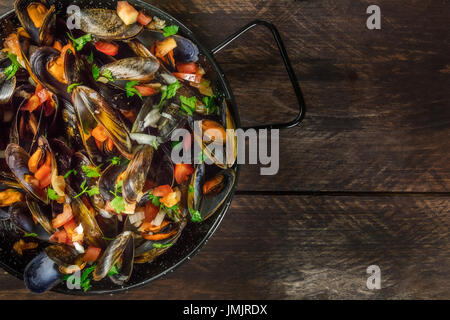 A full skillet of marinara mussels, shot from above on a dark rustic background with a place for text - Stock Photo