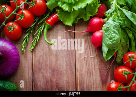 Fresh ingredients for cooking in rustic setting: Salad, radish, Onion, corn, tomatoes, garlic, carrots, cucumber, - Stock Photo