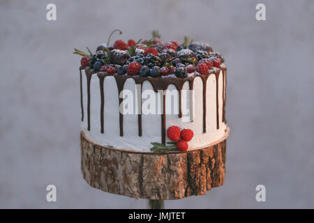 A wedding cake with berries, poured with chocolate on a shelf made of wood - Stock Photo