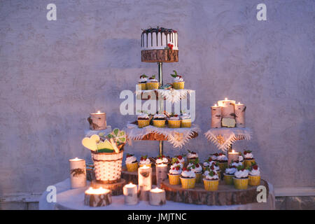 Wedding cake and cupcakes with candles on a shelf made of wood - Stock Photo