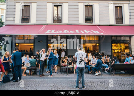 A busy street corner in Milan, Italy during the summer featuring the famous 'Radestsky' bar - Stock Photo