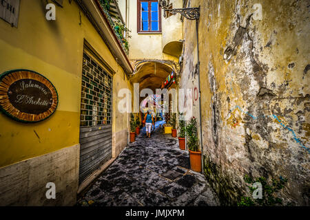 A woman traveling alone walks down a narrow path through a small tunnel in the Mediterranean city of Sorrento Italy - Stock Photo