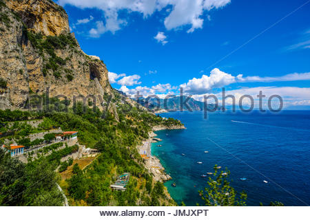 The Amalfi Coast near Positano and Sorrento on a warm summer afternoon with boats in the water and homes and resorts - Stock Photo