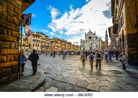 Late summer afternoon in the Tuscan city of Florence as tourists walk through Piazza Santa Croce towards the Basilica - Stock Photo