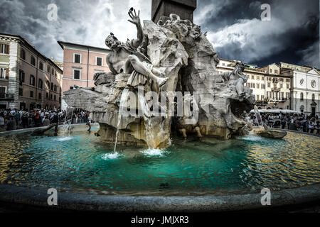 The Fountain of the Four Rivers by Bernini in the Piazza Navona in Rome Italy. The skies are dark with a storm coming. - Stock Photo
