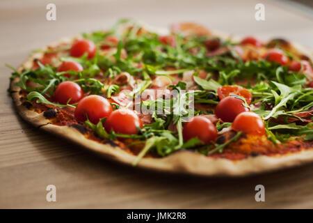 Tasty pizza with cherry tomato ham rucola , homemade prepared food. - Stock Photo