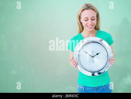 Digital composite of Woman holding clock in front of green background - Stock Photo