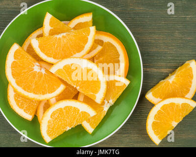 Freshly Cut Juicy Orange Slices or Segments Against a Green Wooden Background - Stock Photo