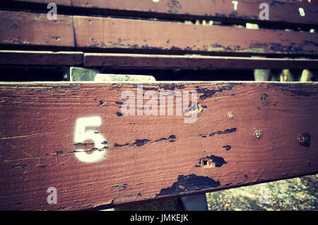 Number five painted on an old wooden seat, conceptual picture with copy space on the right. - Stock Photo