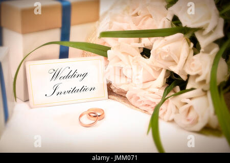 Wedding Invitation card with rings, presents and roses - Stock Photo