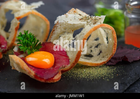 Cured meat on crusty bread with yolk and parmegano cheese, close view, selective focus - Stock Photo