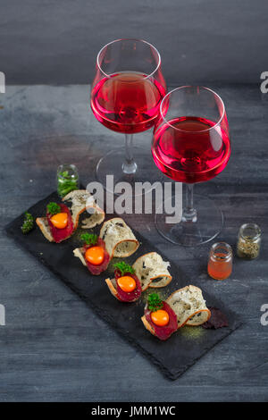 Appetizers - cured meat, crusty bread, yolk and cheese - on stone board with two glasses of wine - Stock Photo