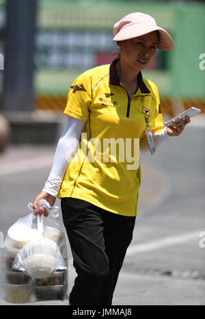 Chongqing, China. 28th July, 2017. A food delivery woman is seen in Jiangbei District in Chongqing, southwest China, - Stock Photo