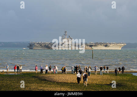 Gosport, UK. 27th July, 2017. Gosport, Hamphshire, England, UK. People flock to see USS George HW Bush, American Super Nimitz class aircraft carrier off Stokes Bay, Gosport, Lee-on-Solent Hampshire overlooking the Isle of Wight. The warship cost £4.7 billion, has 5500 personnel, weighs 97,000 tonnes and measurres 1092ft long . Credit: Prixpics/Alamy Live News