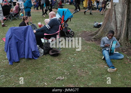 Cambridge, UK. 28th July, 2017. A child sits against a tree and plays the Bodhran at the Cambridge Folk Festival. - Stock Photo