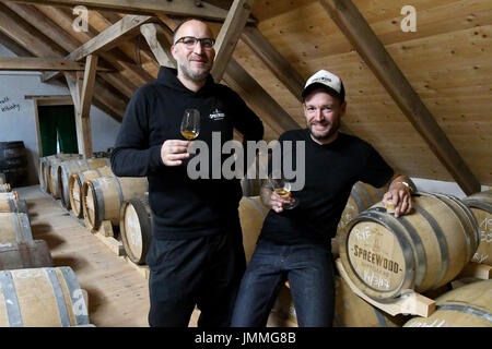 Schlepzig, Germany. 26th July, 2017. Owners Steffen Lohr (l) and Bastian Heuser test a whiskey in their storage - Stock Photo