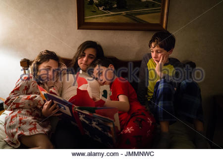 Two girls and two boys read bed time stories in their pajamas in bed. - Stock Photo
