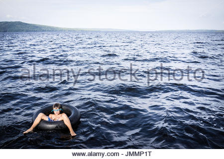A young boy, wearing blue goggles, floats in an innertube on an empty lake. - Stock Photo