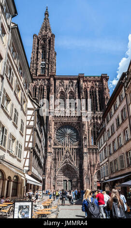 People, mainly tourists, in Rue Mercière, walking towards the west facade of Cathédrale Notre-Dame de Strasbourg - Stock Photo