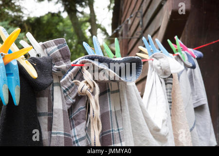 Washing Hanging on a Red Washing Line in Domestic / Natural Setting - Stock Photo