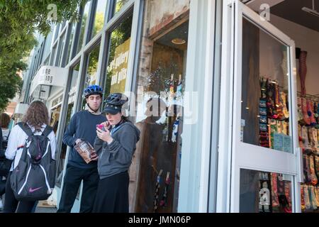 Two Millennial age cyclists wearing helmets stand outside a store on Bridgeway road in downtown Sausalito, California, - Stock Photo