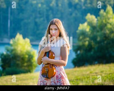 Young female violinist in nature near edge lake alone lonesome solitude loneliness innocent look innocence silence - Stock Photo