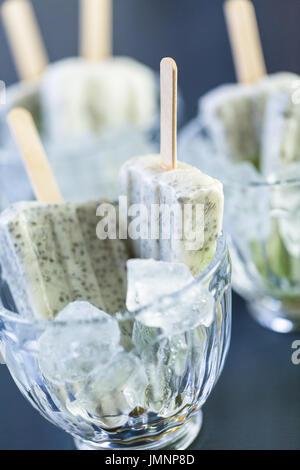 Kiwi coconut chia popsicles in glass ice cream cups. - Stock Photo