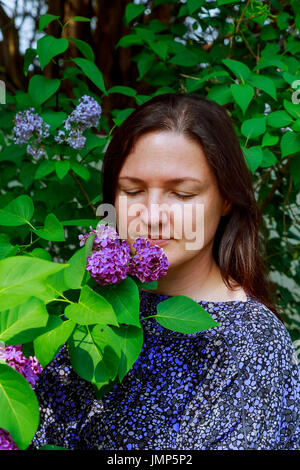 Girl enjoys wonderful smell of lilac. Curly light below her shoulders, long white dress, summer hat with basket - Stock Photo