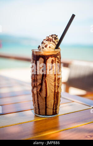 Iced blended milk and chocolate frappucino with whipped cream on beach - Stock Photo