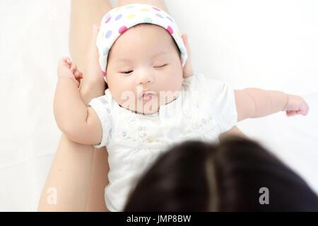 Portrait of adorable baby sleeping on mother hand - Stock Photo