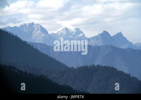 Morning mountain landscape with layer of mountain peaks covered with coniferous deciduous forests. View from Dochula - Stock Photo