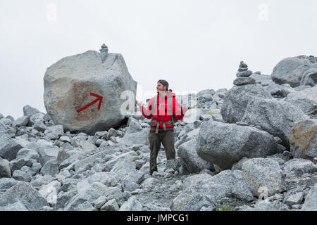 The trail is marked with two large cairns and a giant red arrow painted on a boulder, but this man appears to be - Stock Photo